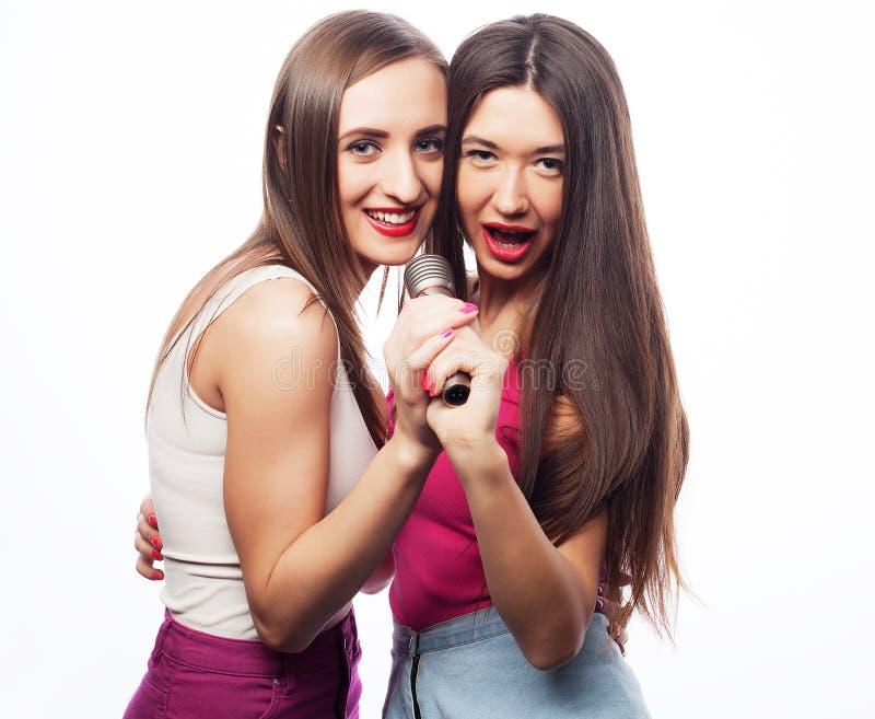 Conceito do estilo de vida, da felicidade, o emocional e dos povos: meninas do moderno da beleza com um microfone fotos de stock