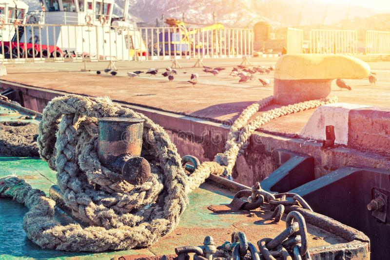 Conceito do estilo de vida estabelecido e do domicílio permanente - a corda da amarração mantém o navio em um lugar no porto em u foto de stock