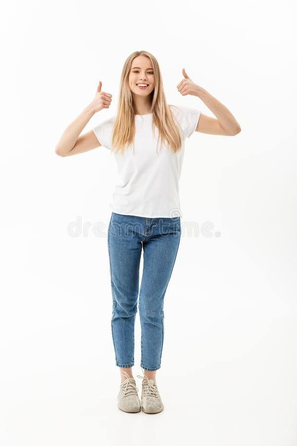 Conceito do estilo de vida: A jovem mulher de sorriso feliz nas calças de brim que olham a câmera que dá um dobro manuseia acima  imagens de stock royalty free