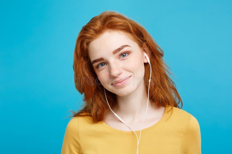 Conceito do estilo de vida - o retrato da menina vermelha do cabelo do gengibre feliz alegre aprecia escutar a música com os fone imagens de stock royalty free