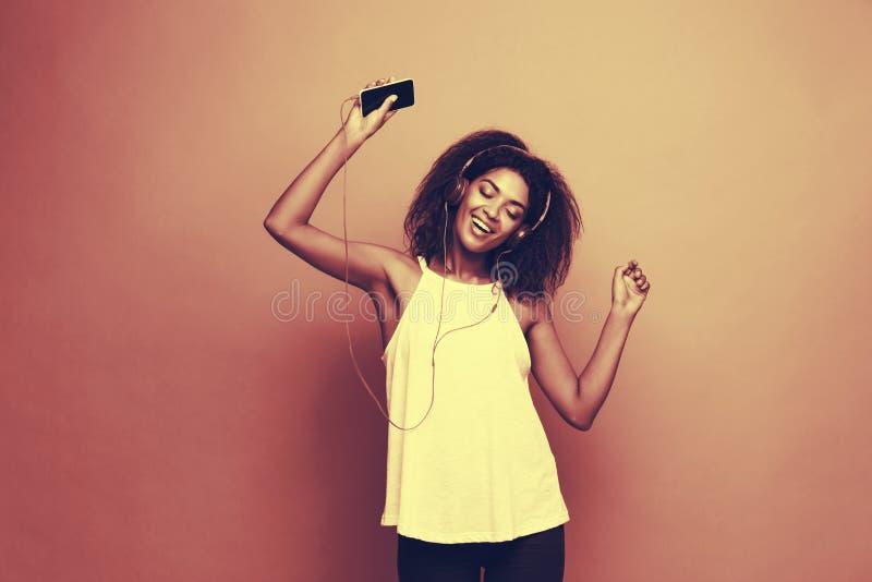 Conceito do estilo de vida - retrato da escuta alegre da mulher afro-americano bonita a música no telefone celular amarelo fotografia de stock