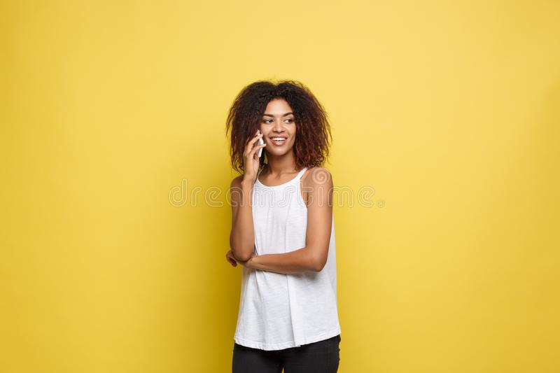 Conceito do estilo de vida - retrato da fala alegre da mulher afro-americano bonita no telefone celular com amigo amarelo foto de stock