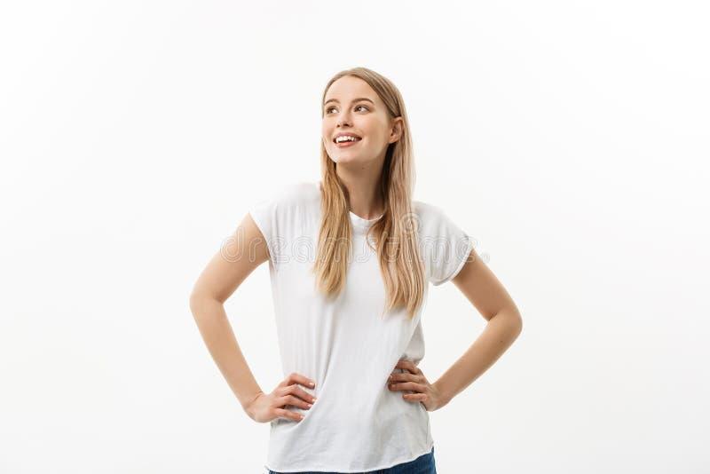Conceito do estilo de vida: Retrato da jovem mulher surpreendida loura feliz no fundo branco imagem de stock