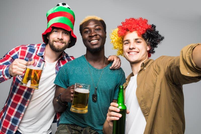 Conceito do fã de futebol do futebol do funtime do lazer dos feriados Três indivíduos alegres entusiasmados amigáveis da raça mis foto de stock