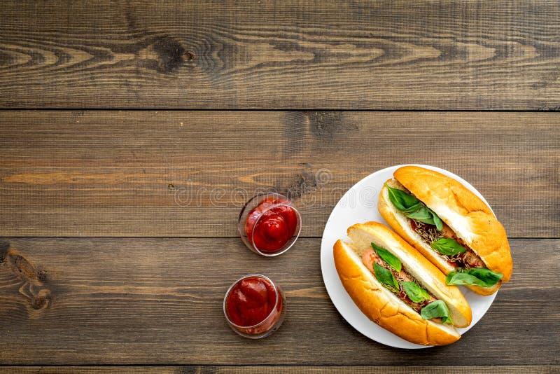 Conceito do Fastfood Faça hotdogs e a casa frescos bolo para cachorros quentes com salsichas do freid e manjericão perto do sause fotografia de stock royalty free