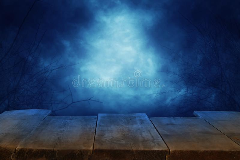 Conceito do feriado de Dia das Bruxas Esvazie a tabela rústica na frente do fundo assustador e enevoado do céu noturno Apronte pa imagens de stock