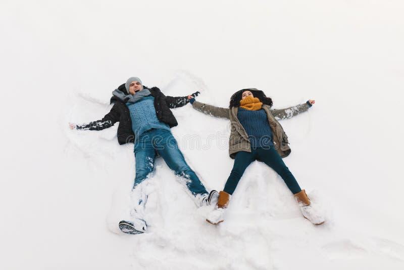 Conceito do feriado de inverno - encontro do homem e da mulher feliz na neve branca fotografia de stock royalty free