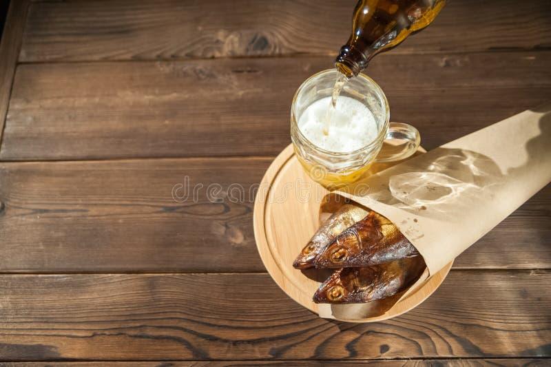 Conceito do feriado de Oktoberfest Cerveja, peixe fumado, microplaquetas em um fundo estrutural de madeira em uma chave escura Ce fotografia de stock