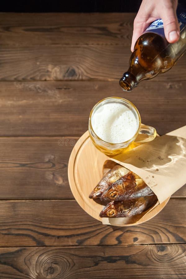 Conceito do feriado de Oktoberfest Cerveja, peixe fumado, microplaquetas em um fundo estrutural de madeira em uma chave escura Ce fotos de stock royalty free