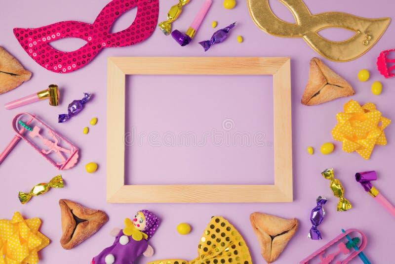 Conceito do feriado de Purim com quadro de madeira, máscara do carnaval e cookies das orelhas dos hamans no fundo roxo Vista supe imagens de stock