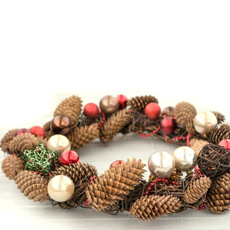 Conceito do feriado Grinalda decorativa do Natal com bolas e os cones vermelhos a bordo Ano novo feliz Copie o espaço fotografia de stock