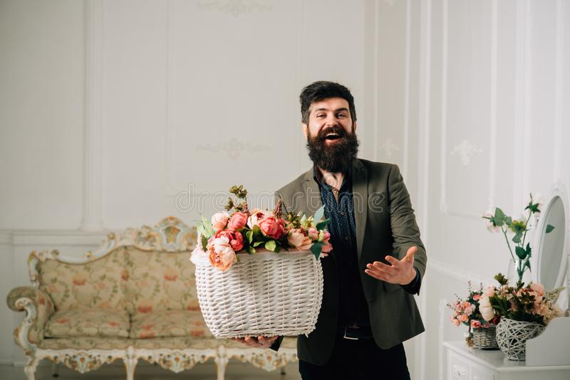 Conceito do feriado Sorriso do moderno com ramalhete do feriado Homem feliz com as flores na cesta para o feriado Cumprimentos do foto de stock
