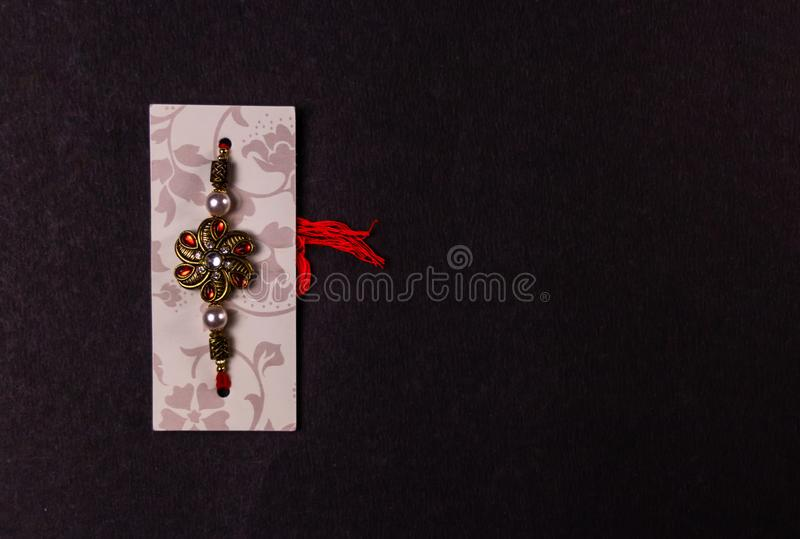 Conceito do festival de Raksha Bandhan - desenhista Rakhi ou faixa de pulso isolada no fundo preto Rakhi - símbolo do amor no mei foto de stock
