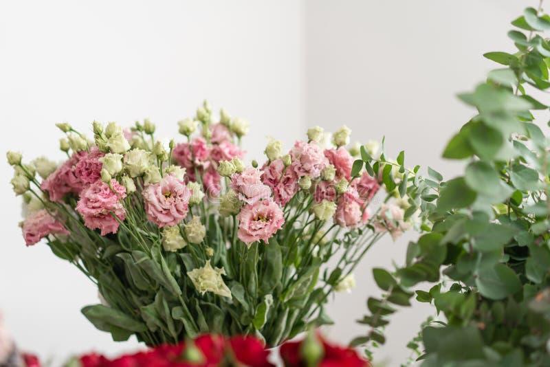 Conceito do florista Vasos com as flores diferentes na tabela de madeira wallpaper imagens de stock