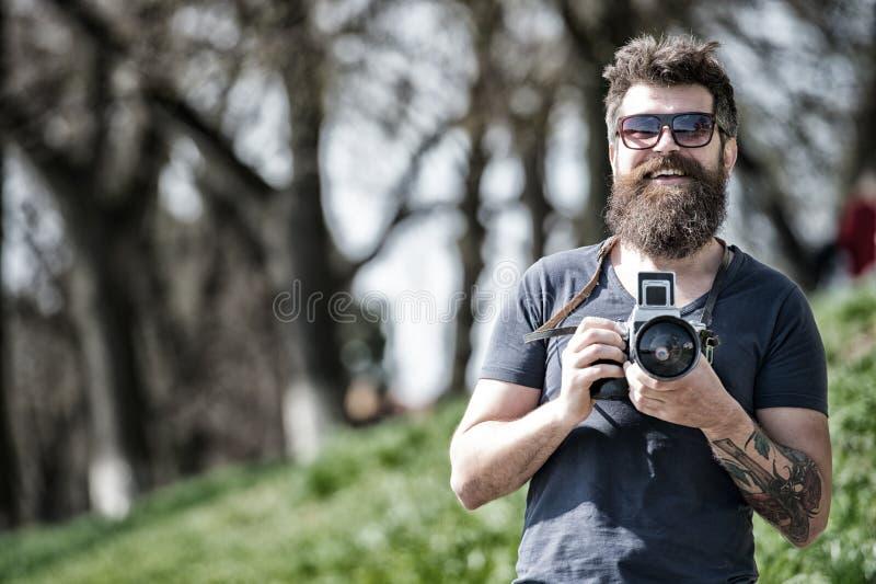 Conceito do fotógrafo Câmera farpada do vintage da posse do fotógrafo do moderno do homem Fotógrafo com o amador da barba e do bi imagem de stock