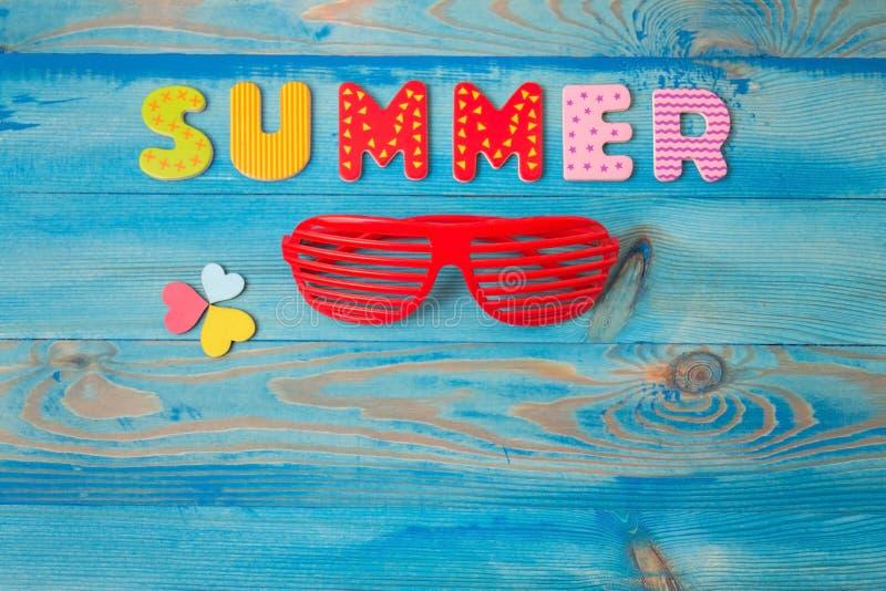 Conceito do fundo das férias de verão da vista superior com máscaras louvered e corações de madeira na tabela de madeira azul foto de stock