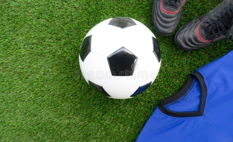Conceito do futebol: Bola de futebol do futebol, botas velhas do futebol, azuis foto de stock