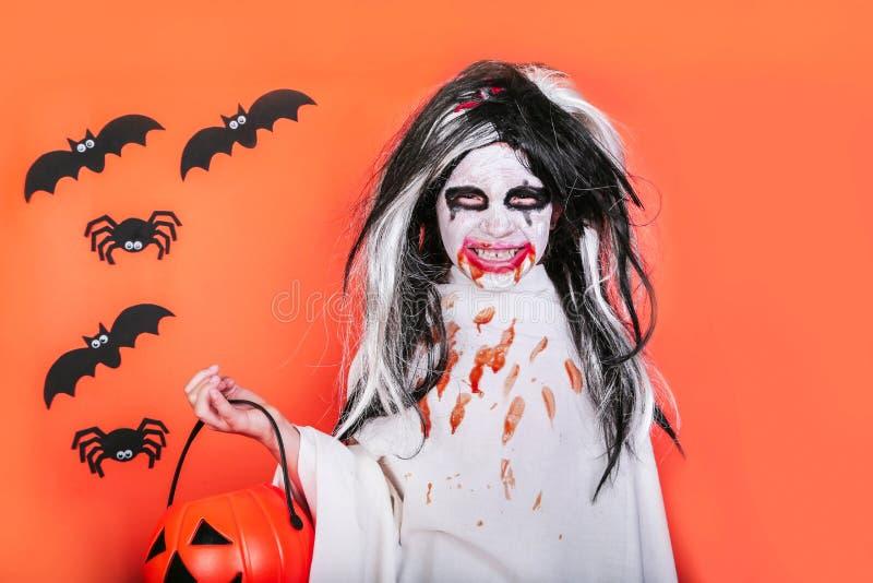Conceito do horror de Halloween Menina assustador pequena bonito no traje do zombi do monstro com a abóbora no fundo alaranjado fotografia de stock royalty free