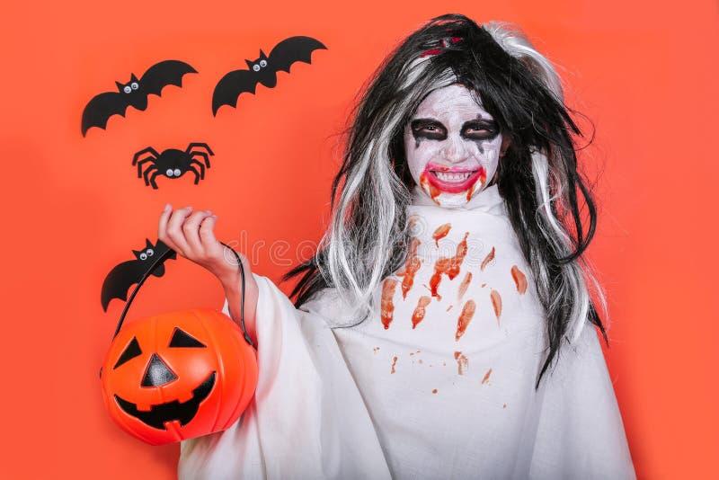 Conceito do horror de Halloween Menina assustador pequena bonito no traje do zombi do monstro com a abóbora no fundo alaranjado imagem de stock royalty free