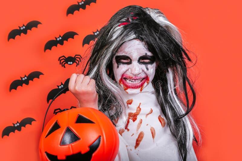 Conceito do horror de Halloween Menina assustador pequena bonito no traje do zombi do monstro com a abóbora no fundo alaranjado imagem de stock