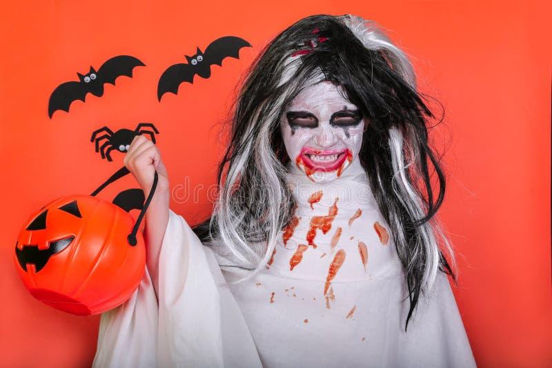 Conceito do horror de Halloween Menina assustador pequena bonito no traje do zombi do monstro com a abóbora no fundo alaranjado fotos de stock