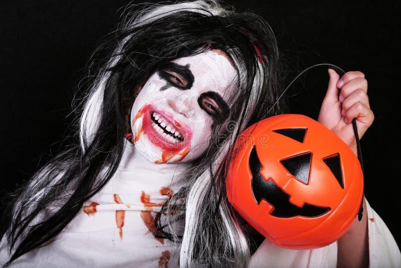 Conceito do horror de Halloween Menina assustador pequena bonito no traje do zombi do monstro com a abóbora no fundo preto foto de stock