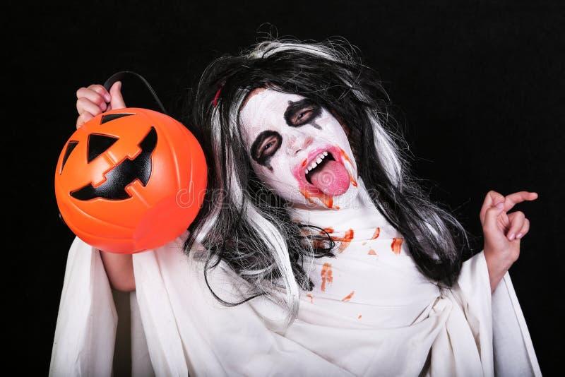 Conceito do horror de Halloween Menina assustador pequena bonito no traje do zombi do monstro com a abóbora no fundo preto foto de stock royalty free