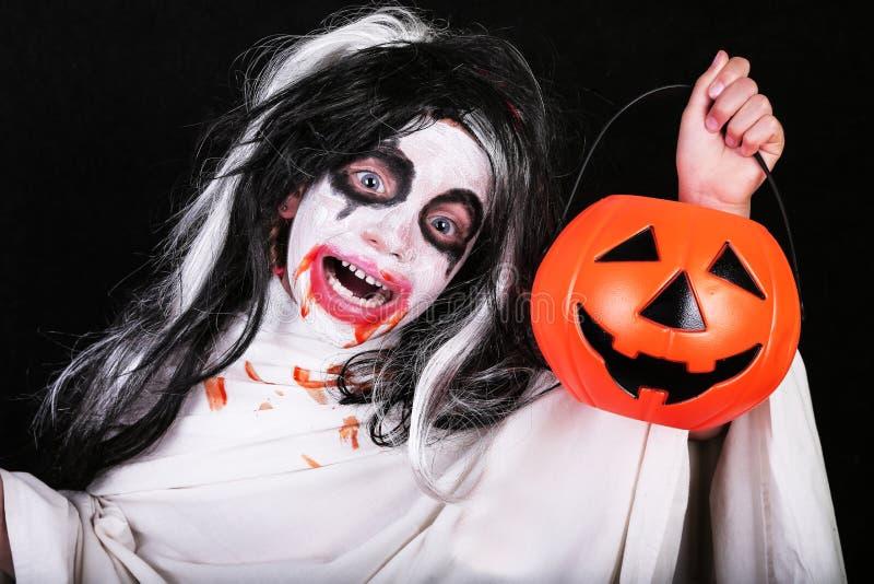 Conceito do horror de Halloween Menina assustador pequena bonito no traje do zombi do monstro com a abóbora no fundo preto imagens de stock