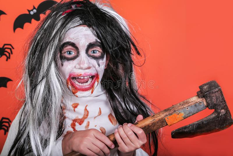 Conceito do horror de Halloween Menina assustador pequena bonito no traje do zombi do monstro com machado e sangue no fundo alara foto de stock royalty free