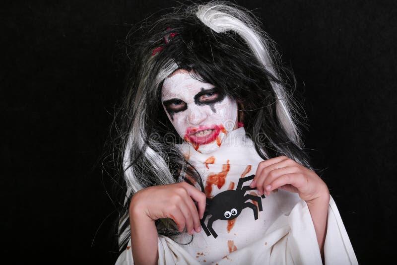 Conceito do horror de Halloween Menina assustador pequena bonito no traje do zombi do monstro no fundo preto imagem de stock
