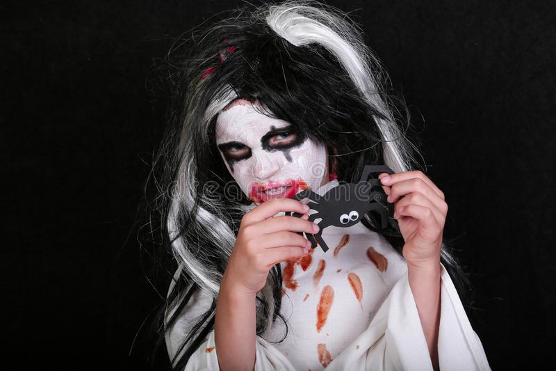 Conceito do horror de Halloween Menina assustador pequena bonito no traje do zombi do monstro no fundo preto fotografia de stock royalty free