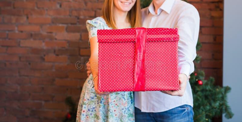 Conceito do inverno, dos feriados, do Natal e dos povos - próximo acima de pares felizes com presente do Natal em casa imagem de stock