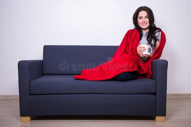 Conceito do inverno - jovem mulher que senta-se no sofá com a caneca de wra do chá fotos de stock royalty free