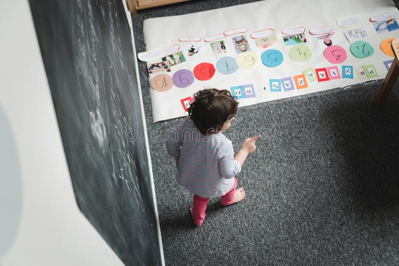 Conceito do jardim de infância Desenho pré-escolar feliz da menina no quadro-negro e no divertimento ter imagem de stock