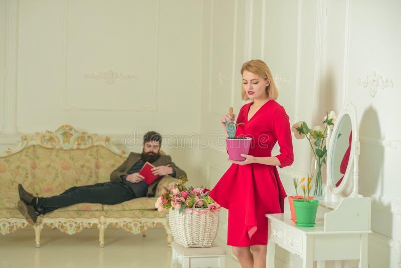 Conceito do jardineiro Mulher e homem no sofá O jardineiro bonito toma da planta e do moderno que leem um livro Jardineiro com imagem de stock