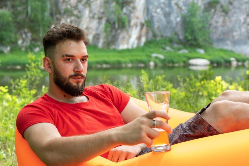 Conceito do lazer, acampando, férias de verão Homem caucasiano farpado novo com os vidros da cerveja que colocam no sofá alaranja fotografia de stock