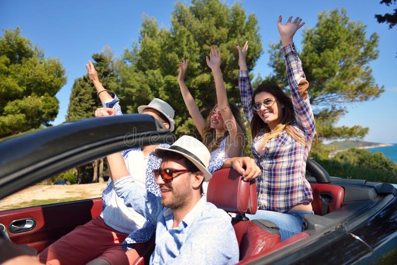 Conceito do lazer, da viagem por estrada, do curso e dos povos - amigos felizes que conduzem no carro do cabriolet ao longo da es fotos de stock