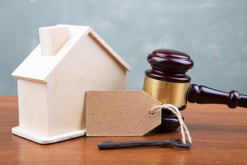 Conceito do leilão da venda dos bens imobiliários - o martelo e a casa modelam na tabela de madeira imagem de stock