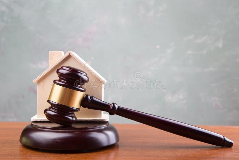 Conceito do leilão da venda dos bens imobiliários - o martelo e a casa modelam na tabela de madeira imagem de stock royalty free
