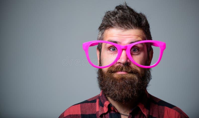 Conceito do lerdo Moderno que olha completamente de monóculos cor-de-rosa gigantes A barba do homem e a cara do bigode vestem mon fotografia de stock