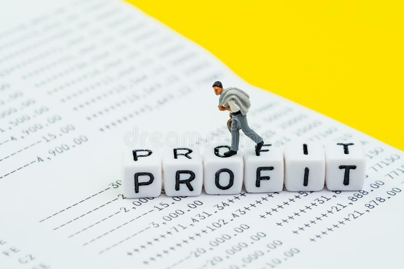 Conceito do lucro do negócio, do investimento ou da empresa, homem de negócios diminuto que anda no bloco do cubo com lucro da pa imagens de stock