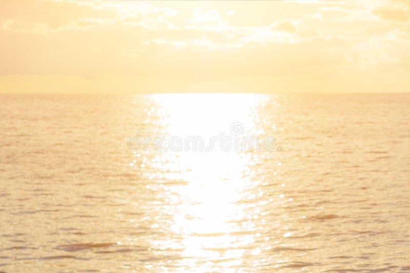Conceito do mar do alvorecer: Fundo da textura do por do sol da luz de Sun e da praia do borrão fotos de stock royalty free