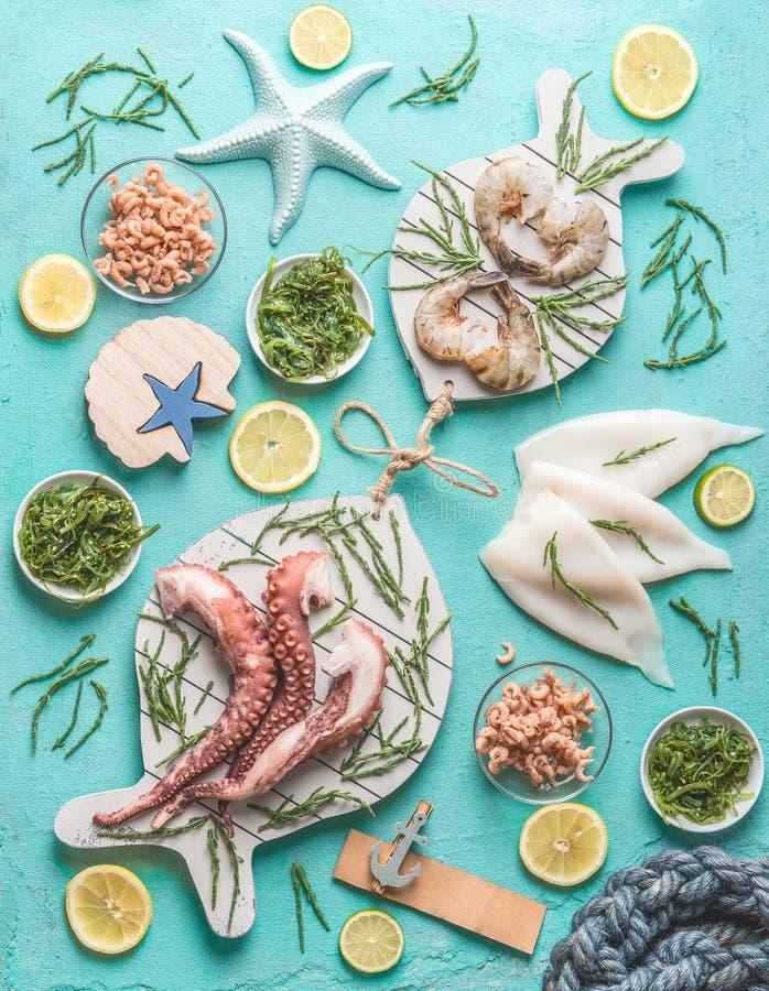 Conceito do marisco Vário marisco na luz - fundo azul, decorado com algas, vista superior foto de stock royalty free