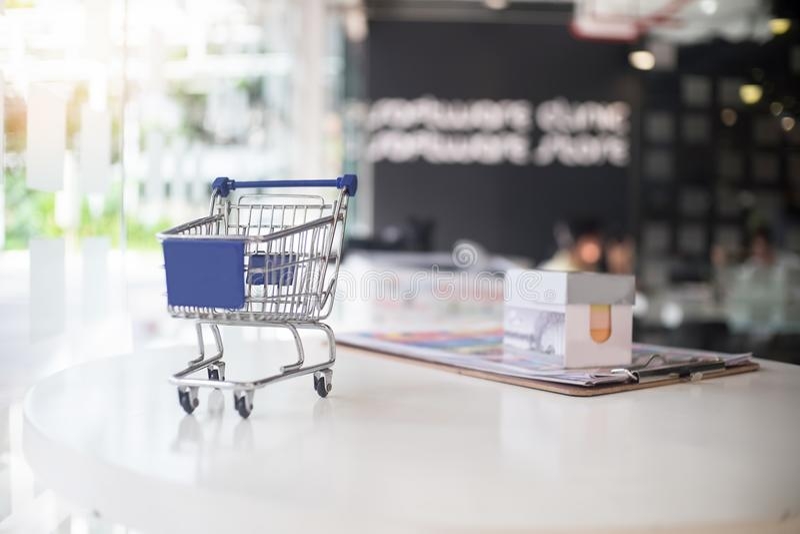 Conceito do mercado, pouco carrinho de compras na tabela imagem de stock