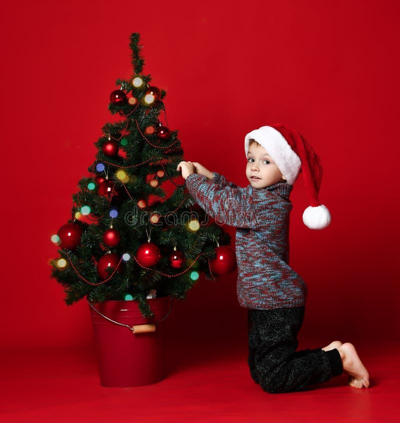 Conceito do Natal Ano novo a criança veste acima uma árvore de Natal Brinquedos das crianças e do Natal imagens de stock