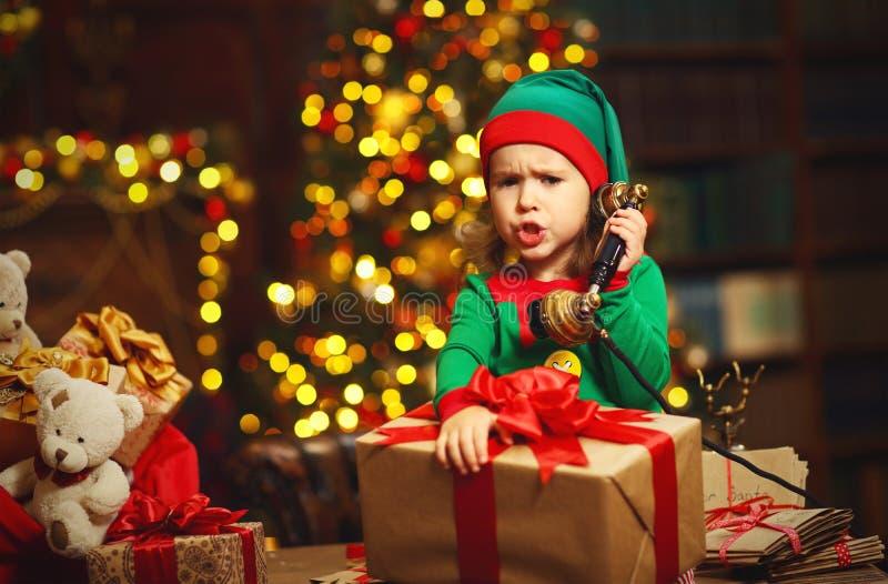Conceito do Natal Funcionamento da criança do duende, falando no telefone fotografia de stock royalty free