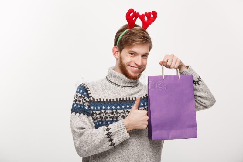 Conceito do Natal - homem considerável novo da barba feliz com o saco de compras na mão isolada no branco fotos de stock royalty free