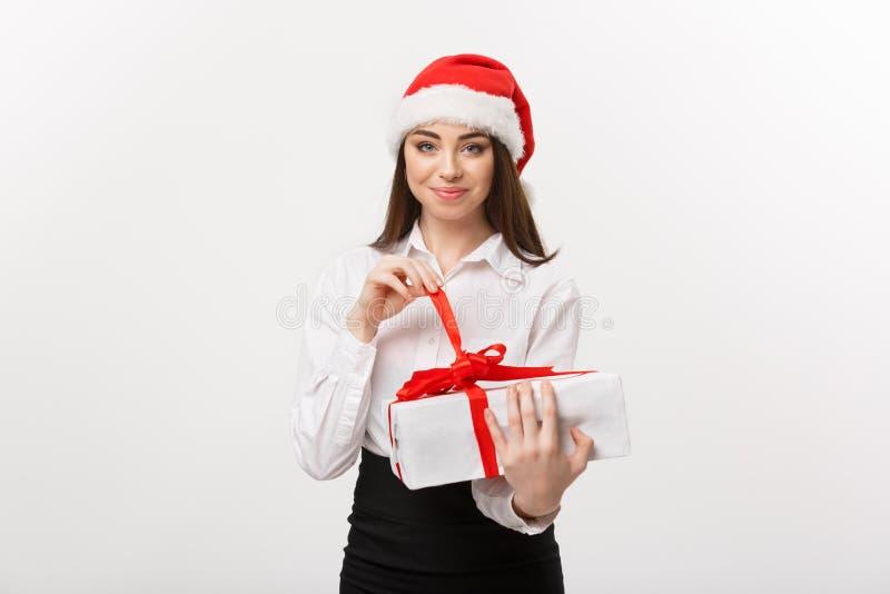 Conceito do Natal - mulher de negócio caucasiano feliz nova com chapéu de Santa que sorri quando caixa de presente aberta com esp fotos de stock