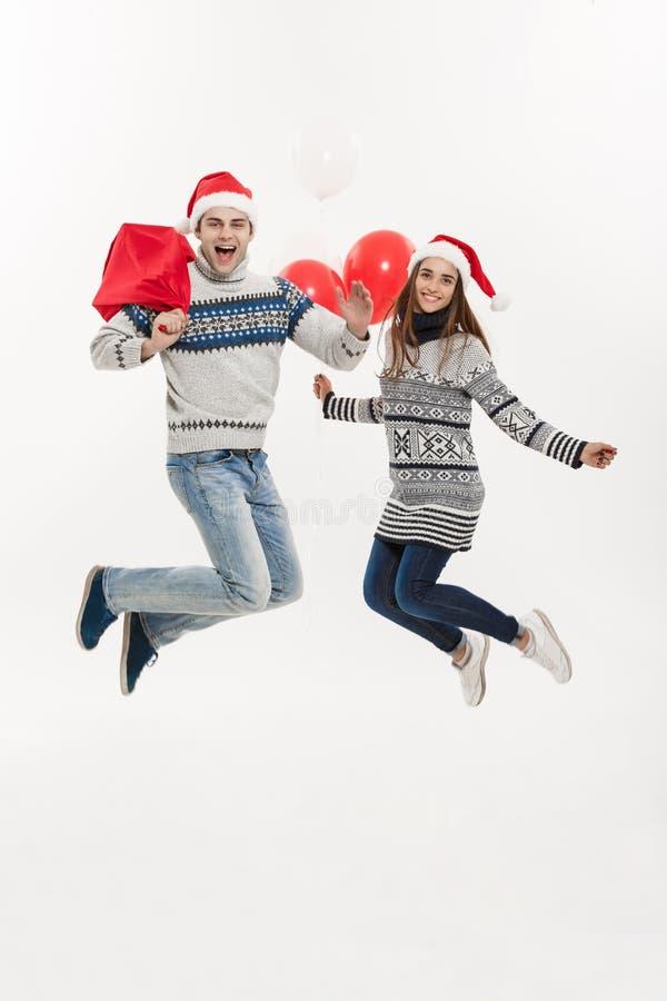 Conceito do Natal - par atrativo novo do comprimento completo que guardam o saco de Santa e balão isolado no fundo cinzento branc imagem de stock royalty free