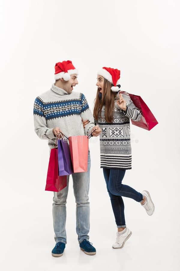 Conceito do Natal - par atrativo novo do comprimento completo que mantém sacos de compras isolados no fundo cinzento branco foto de stock